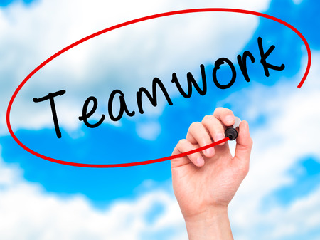 synergism: Man Hand writing Teamwork with black marker on visual screen. Isolated on sky. Business, technology, internet concept. Stock Image