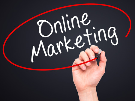 meta data: Man Hand writing Online Marketing with black marker on visual screen. Isolated on black. Business, technology, internet concept. Stock Image Stock Photo