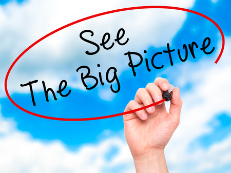 big picture: Man Hand writing See The Big Picture with black marker on visual screen. Isolated on sky. Business, technology, internet concept. Stock Image