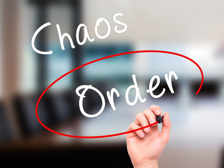 order chaos: Man Hand writing and Choosing Order instead of Chaos with black marker on visual screen. Isolated on office. Business, technology, internet concept. Stock Image