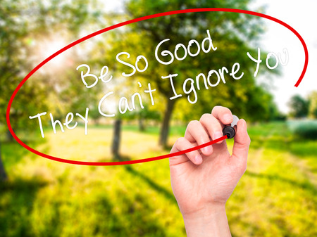 ignore: Man Hand writing Be So Good They Cant Ignore You with black marker on visual screen. Isolated on background. Business, technology, internet concept. Stock Photo