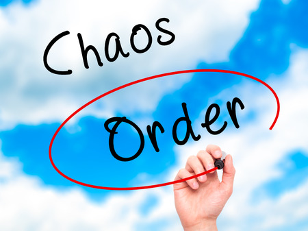 chaos order: Man Hand writing and Choosing Order instead of Chaos with black marker on visual screen. Isolated on sky. Business, technology, internet concept. Stock Image Stock Photo