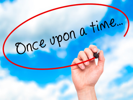 phrase novel: Man Hand writing Once upon a time... with black marker on visual screen. Isolated on sky. Business, technology, internet concept. Stock Image
