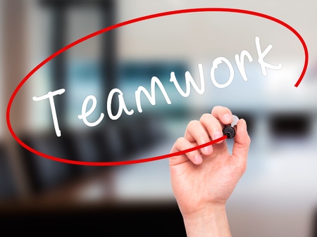 synergism: Man Hand writing Teamwork with black marker on visual screen. Isolated on office. Business, technology, internet concept. Stock Image
