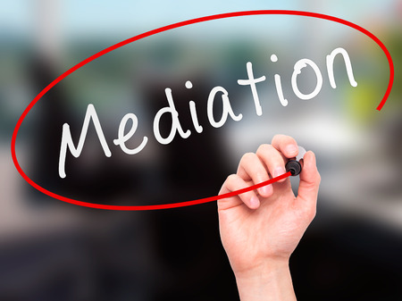 mediate: Man Hand writing Mediation with marker on transparent wipe board. Isolated on office. Business, internet, technology concept.  Stock Photo