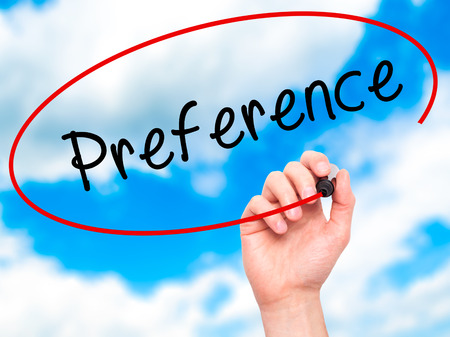 preference: Man Hand writing Preference with black marker on visual screen. Isolated on sky. Business, technology, internet concept. Stock Image
