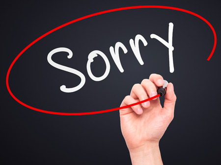 regretful: Man Hand writing Sorry with marker on transparent wipe board. Isolated on black. Business, internet, technology concept.  Stock Photo