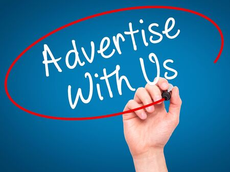 advertise: Man Hand writing Advertise With Us  with black marker on visual screen. Isolated on blue. Business, technology, internet concept. Stock Image Stock Photo