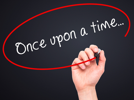 phrase novel: Man Hand writing Once upon a time... with black marker on visual screen. Isolated on black. Business, technology, internet concept. Stock Image