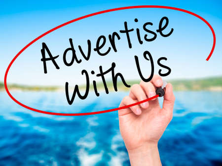 advertise with us: Man Hand writing Advertise With Us  with black marker on visual screen. Isolated on nature. Business, technology, internet concept. Stock Image