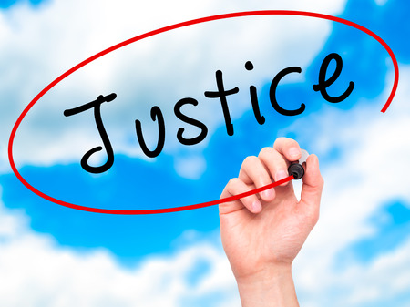 fair trial: Man Hand writing Justice with black marker on visual screen. Isolated on sky. Business, technology, internet concept. Stock Image Stock Photo