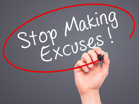 justify: Man Hand writing Stop Making Excuses with black marker on visual screen. Isolated on grey. Business, technology, internet concept. Stock Image