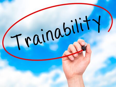 able to learn: Man Hand writing Trainability with black marker on visual screen. Isolated on sky. Business, technology, internet concept. Stock Image