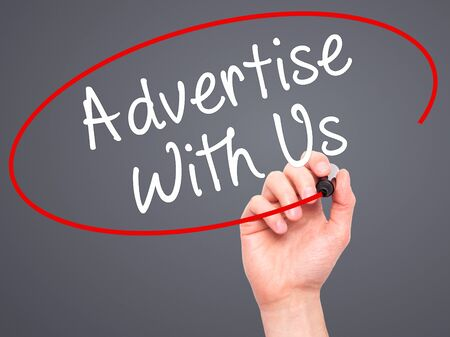 advertise with us: Man Hand writing Advertise With Us  with black marker on visual screen. Isolated on grey. Business, technology, internet concept. Stock Image