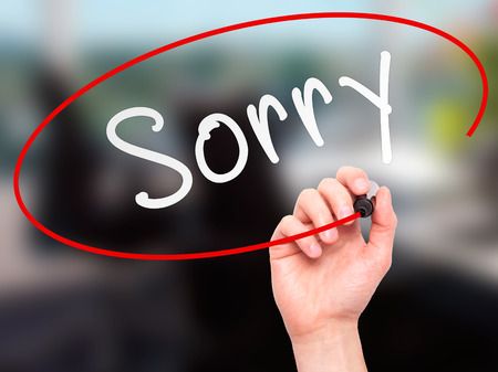 bad pardon: Man Hand writing Sorry with marker on transparent wipe board. Isolated on office. Business, internet, technology concept.  Stock Photo Stock Photo