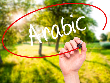 theology: Man Hand writing Arabic  with black marker on visual screen. Isolated on background. Business, technology, internet concept. Stock Photo