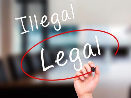 Man mano la scrittura e la scelta legale invece di illegale con pennarello nero su schermo visivo. Isolato su ufficio. Affari, tecnologia, il concetto di internet. Immagine Stock Archivio Fotografico