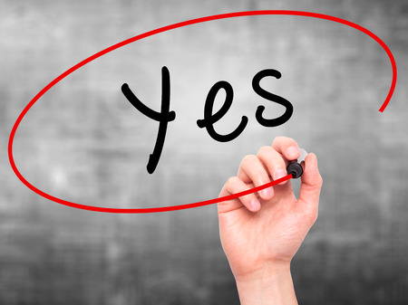 answer approve of: Man Hand writing Yes with black marker on visual screen. Isolated on grey. Business, technology, internet concept. Stock Image Stock Photo