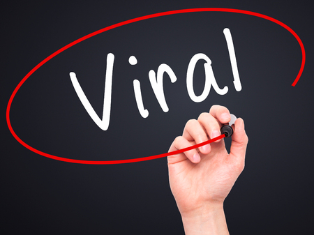 web cast: Man Hand writing Viral with black marker on visual screen. Isolated on black. Business, technology, internet concept. Stock Image