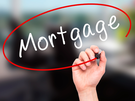 creditworthiness: Man Hand writing Mortgage with black marker on visual screen. Isolated on office. Business, technology, internet concept. Stock Image