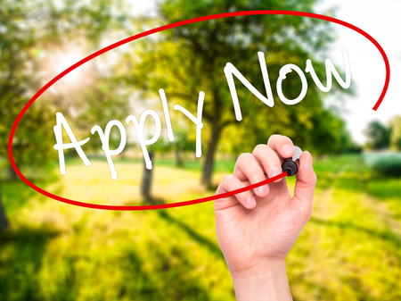 Man Hand writing Apply Now with black marker on visual screen. Isolated on nature. Business, technology, internet concept. Stock Photo