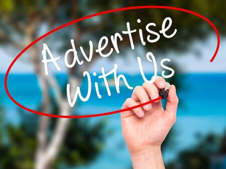 advertise: Man Hand writing Advertise With Us  with black marker on visual screen. Isolated on nature. Business, technology, internet concept. Stock Image