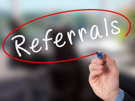 referidos: Man Hand writing Referrals with marker on virtual screen. Business, technology, internet concept. Stock Photo Foto de archivo
