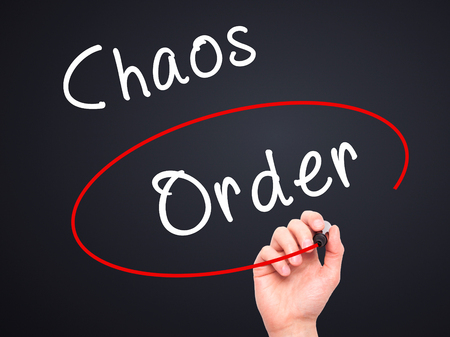chaos order: Man Hand writing and Choosing Order instead of Chaos with black marker on visual screen. Isolated on black. Business, technology, internet concept. Stock Image
