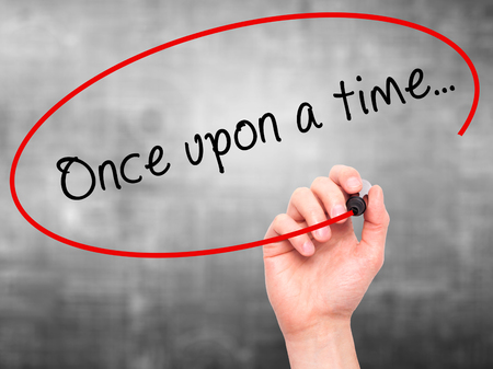 phrase novel: Man Hand writing Once upon a time... with black marker on visual screen. Isolated on grey. Business, technology, internet concept. Stock Image Stock Photo