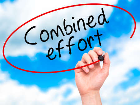 combined effort: Man Hand writing Combined effort with black marker on visual screen. Isolated on sky. Business, technology, internet concept. Stock Image
