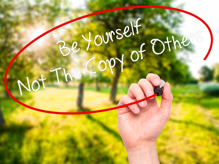 differentiation: Man Hand writing Be Yourself Not The Copy of Others with black marker on visual screen. Isolated on nature. Business, technology, internet concept. Stock Photo