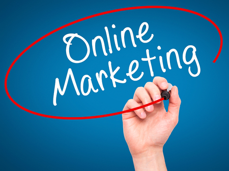 meta data: Man Hand writing Online Marketing with black marker on visual screen. Isolated on blue. Business, technology, internet concept. Stock Image