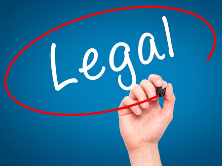 lawful: Man Hand writing Legal with black marker on visual screen. Isolated on blue. Business, technology, internet concept. Stock Image Stock Photo