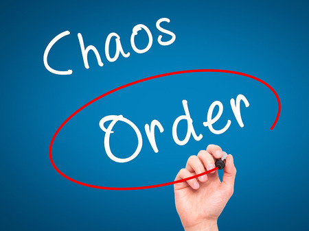 order chaos: Man Hand writing and Choosing Order instead of Chaos with black marker on visual screen. Isolated on blue. Business, technology, internet concept. Stock Image Stock Photo