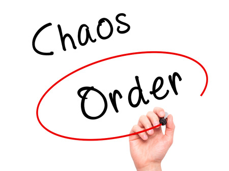 chaos order: Man Hand writing and Choosing Order instead of Chaos with black marker on visual screen. Isolated on white. Business, technology, internet concept. Stock Image