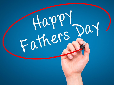 black hand: Man Hand writing Happy Fathers Day with black marker on visual screen. Isolated on blue. Business, technology, internet concept. Stock Image