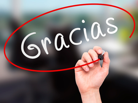 gratitude: Man Hand writing Gracias with marker on transparent wipe board. Isolated on office. Business, internet, technology concept.  Stock Photo