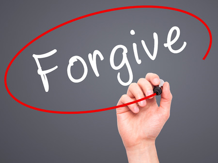 forgiven: Man Hand writing Forgive with black marker on visual screen. Isolated on grey. Business, technology, internet concept. Stock Image