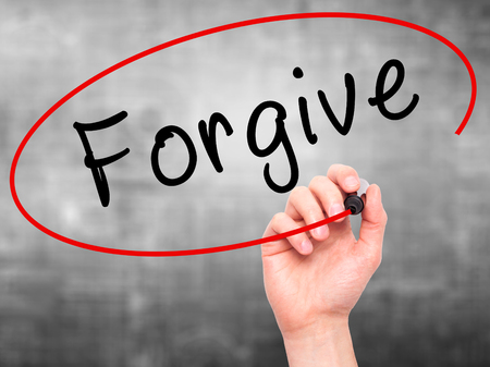 d�livrance: Man Hand writing Forgive with black marker on visual screen. Isolated on grey. Business, technology, internet concept. Stock Image