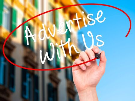 advertise with us: Man Hand writing Advertise With Us  with black marker on visual screen. Isolated on city. Business, technology, internet concept. Stock Image Stock Photo