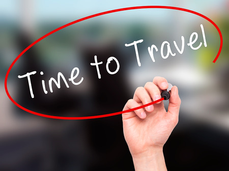 Man Hand writing Time to Travel with black marker on visual screen. Isolated on office. Business, technology, internet concept. Stock Image