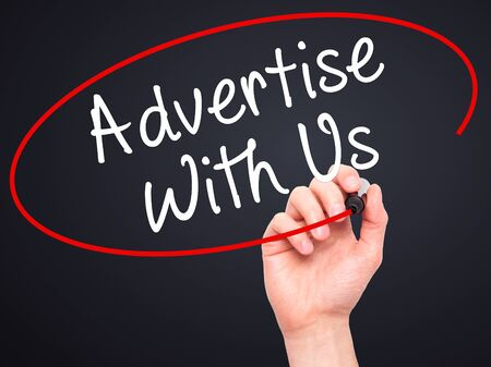 advertise with us: Man Hand writing Advertise With Us  with black marker on visual screen. Isolated on black. Business, technology, internet concept. Stock Image