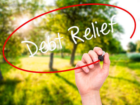 consolidation: Man Hand writing Debt Relief with black marker on visual screen. Isolated on nature. Business, technology, internet concept. Stock Photo