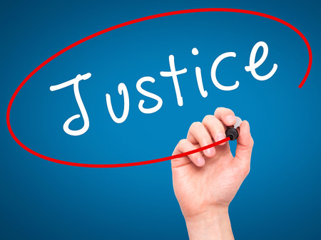 fair trial: Man Hand writing Justice with black marker on visual screen. Isolated on blue. Business, technology, internet concept. Stock Image