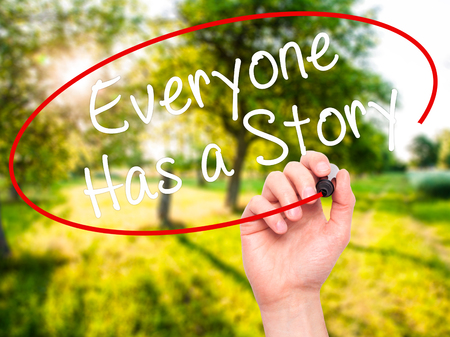 Man Hand writing Everyone Has a Story with black marker on visual screen. Isolated on nature. Business, technology, internet concept. Stock Photo