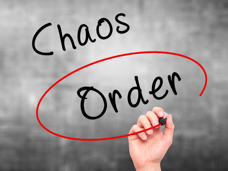 order chaos: Man Hand writing and Choosing Order instead of Chaos with black marker on visual screen. Isolated on grey. Business, technology, internet concept. Stock Image