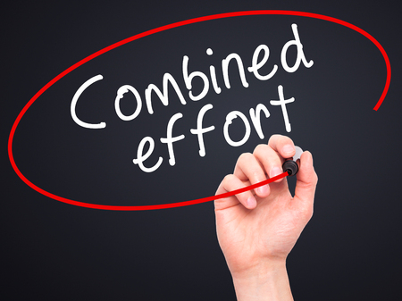 combined effort: Man Hand writing Combined effort with black marker on visual screen. Isolated on black. Business, technology, internet concept. Stock Image