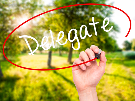 delegar: Man Hand writing Delegate with black marker on visual screen. Isolated on nature. Business, technology, internet concept. Stock Photo