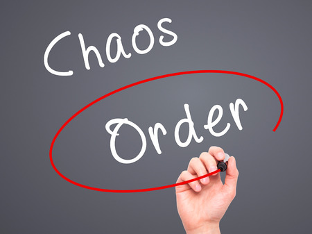 chaos order: Man Hand writing and Choosing Order instead of Chaos with black marker on visual screen. Isolated on grey. Business, technology, internet concept. Stock Image