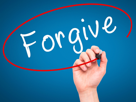 redeeming: Man Hand writing Forgive with black marker on visual screen. Isolated on blue. Business, technology, internet concept. Stock Image